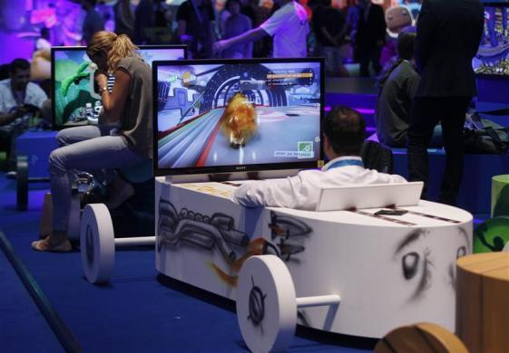 Visitors play a Playstation at an exhibition stand during the Gamescom 2012 fair in Cologne August 15, 2012.