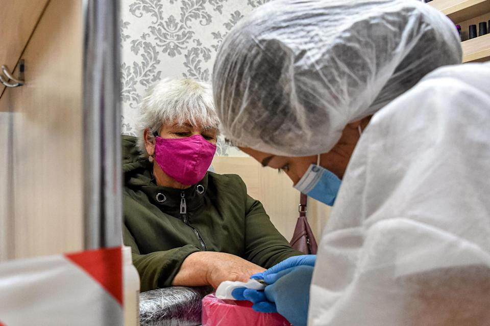 A lady sorts out a customer's nails while wearing protective clothing (AFP via Getty Images)