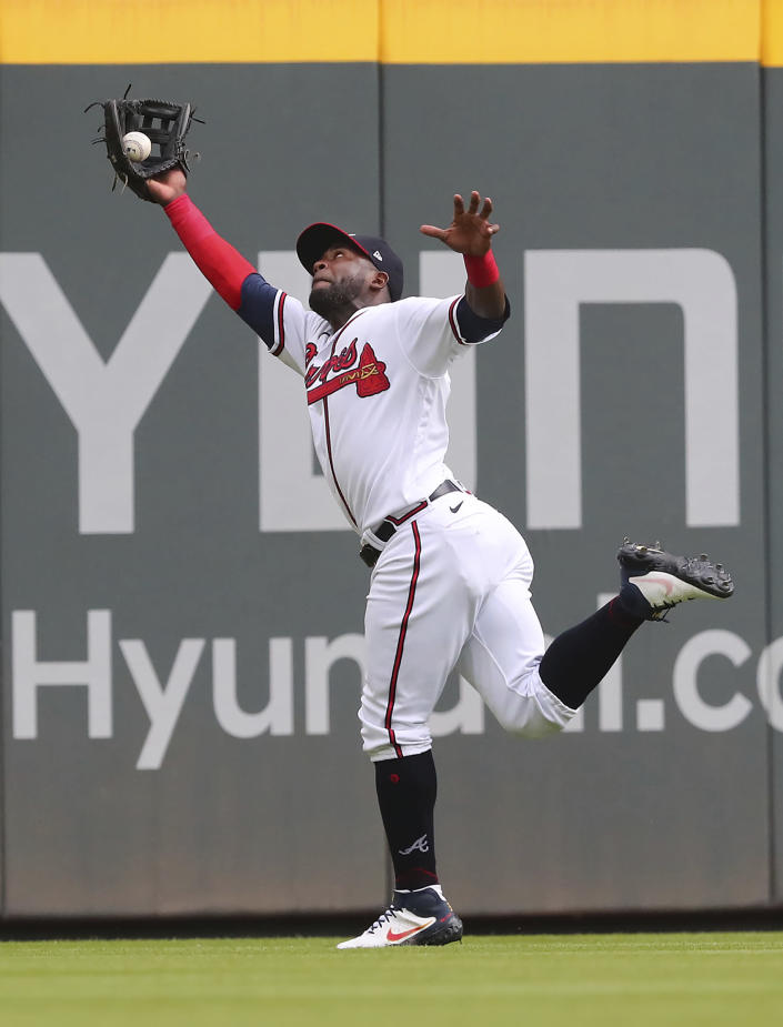 Atlanta Braves outfielder Guillermo Heredia reaches for the baseball, but it bounced out of his glove for a double by San Diego' Padres Trent Grisham during the first inning in the second game of a doubleheader Wednesday, July 21, 2021, in Atlanta. (Curtis Compton/Atlanta Journal-Constitution via AP)