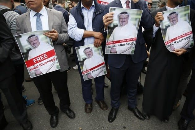 Members of the Turkish-Arab journalist association hold posters with photos of the missing Saudi writer