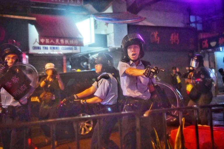 Police officers point their guns at protesters in Tseun Wan in Hong Kong in August