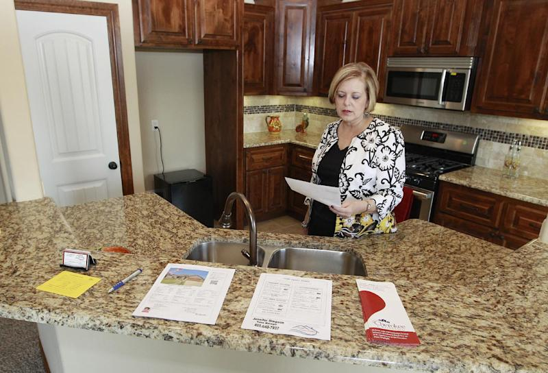 In this Friday, Sept. 21, 2012, photo, Realtor Kimi George is pictured in the kitchen of a home for sale in Oklahoma City. Average U.S. rates on fixed mortgages fell again to new record lows. The decline suggests the Federal Reserve's stimulus efforts may be having an impact on mortgage rates. Mortgage buyer Freddie Mac said Thursday, Sept. 27, 2012, the rate on the 30-year loan dropped to 3.40 percent. That's down from last week's rate of 3.49 percent, which was the lowest since long-term mortgages began in the 1950s. (AP Photo/Sue Ogrocki)