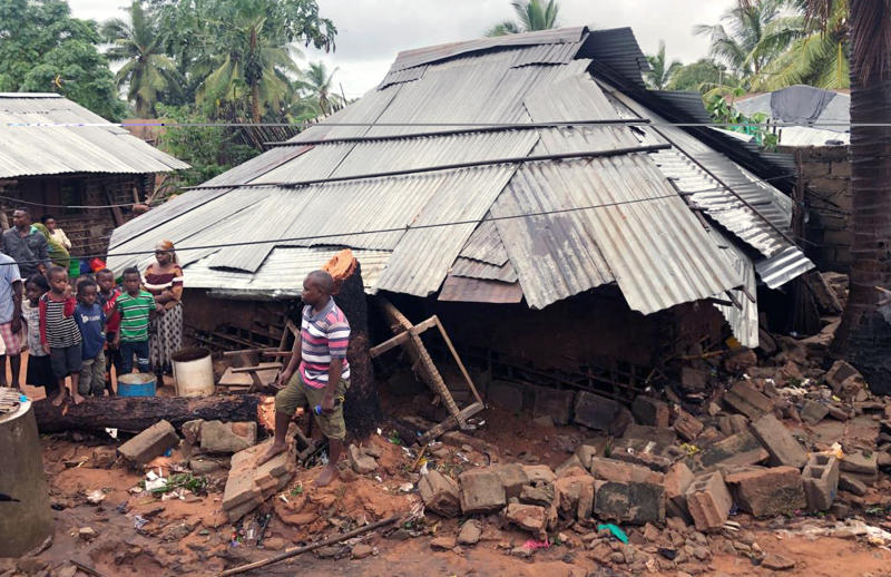 Community members stand near a house where a woman died when her home collapsed due to flooding in Pemba, Mozambique, Sunday, April 28, 2019. Serious flooding began on Sunday in parts of northern Mozambique that were hit by Cyclone Kenneth three days ago, with waters waist-high in areas, after the government urged many people to immediately seek higher ground. Hundreds of thousands of people were at risk. (AP Photo/Tsvangirayi Mukwazhi)