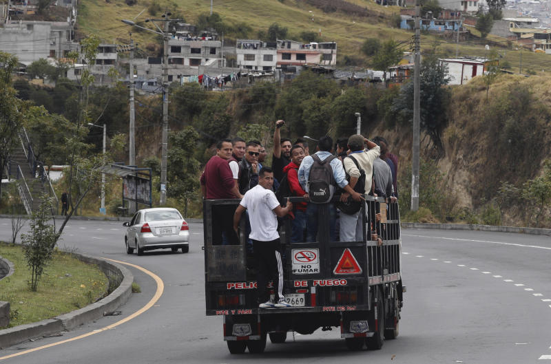 Commuters ride in a trailer during a state of emergency over a transport strike in Quito, Ecuador, Friday, Oct. 4, 2019. Ecuadoran authorities dispatched military vehicles to ferry civilian passengers Friday and arrested several transport union leaders in efforts to halt a strike that shut down taxi, bus and other services in response to a sudden rise in fuel prices. (AP Photo/Dolores Ochoa)