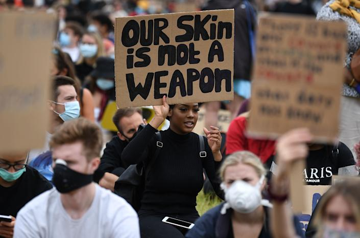 """<i>A protester at an anti-racism demonstration in London on June 3 holds a sign that reads: """"Our skin is not a weapon."""" </i>"""