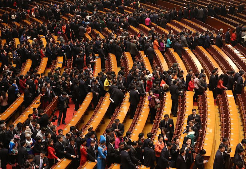 Delegate leave after the opening session of the National People's Congress in Beijing's Great Hall of the People, China, Tuesday, March 5, 2013. China's government promised its people Tuesday deficit-fueled spending to fight deep-seated corruption, improve the despoiled environment and address other quality-of-life issues demanded by an increasingly vocal public looking for change. (AP Photo/Kin Cheung)