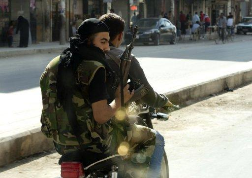 """Syrian rebels armed with their AK-47 ride a motorcycle in the northern city of Aleppo. Regime aircraft hammered insurgent bastions nationwide on Sunday as rebels said they now control most of the country and have moved their command centre from Turkey to """"liberated areas"""" inside Syria"""