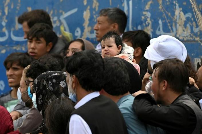 Afghans gather on a roadside near the military part of the airport in Kabul on August 20, 2021, hoping to flee from the country
