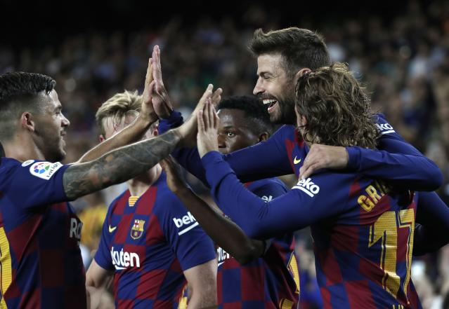 Barcelona's Gerard Pique, second right, celebrates with teammates after scoring his side's third goal during the Spanish La Liga soccer match between FC Barcelona and Valencia CF at the Camp Nou stadium in Barcelona, Spain, Saturday, Sep. 14, 2019. (AP Photo/Joan Monfort)
