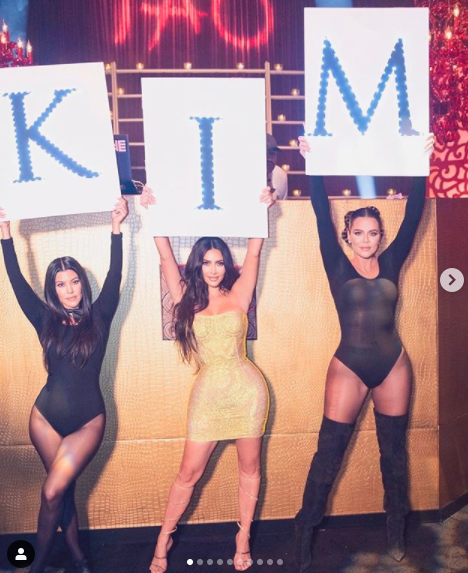 Image of Kourtney, Kim, and Khloe Kardashian holding a 'KIM' sign on Kim's 40th birthday