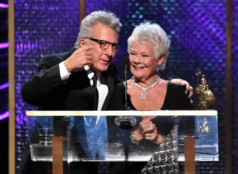 Judi Dench accepts the Albert R. Broccoli Britannia Award for Worldwide Contribution to Entertainment from Dustin Hoffman during the BAFTA Awards on October 30, 2014 in Beverly Hills