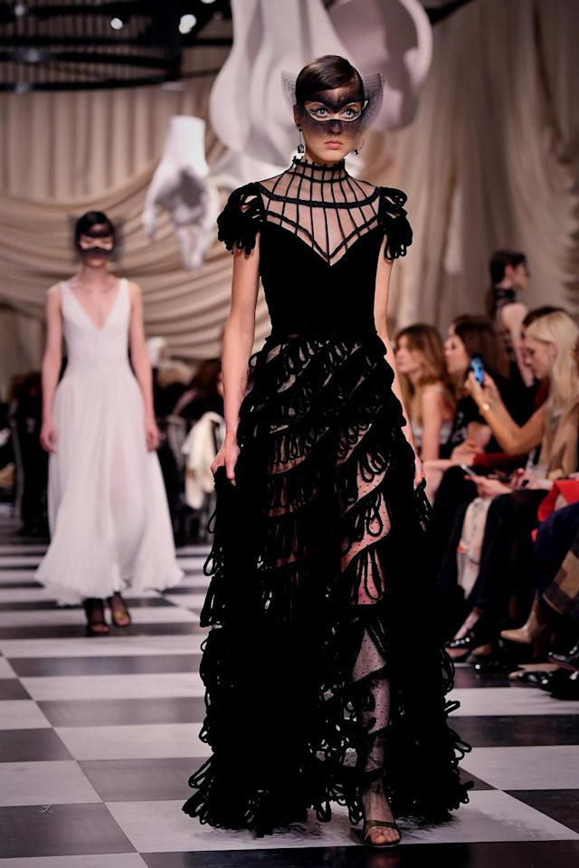 <p>A model wears a black red-carpet-ready tiered gown from the Dior Haute Couture SS18 collection with accompanying mask. (Photo: Getty) </p>