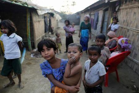 A Rohingya refugee girl carries a baby inside a refugee camp in Sitwe in the state of Rakhine Myanmar