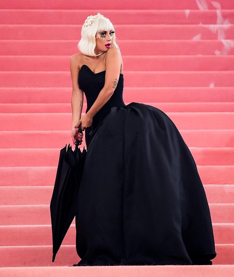 Peeling back the pink gown, Lady Gaga revealed a black dress underneath, complete with a matching umbrella to start phase two of her Met Gala runway performance.