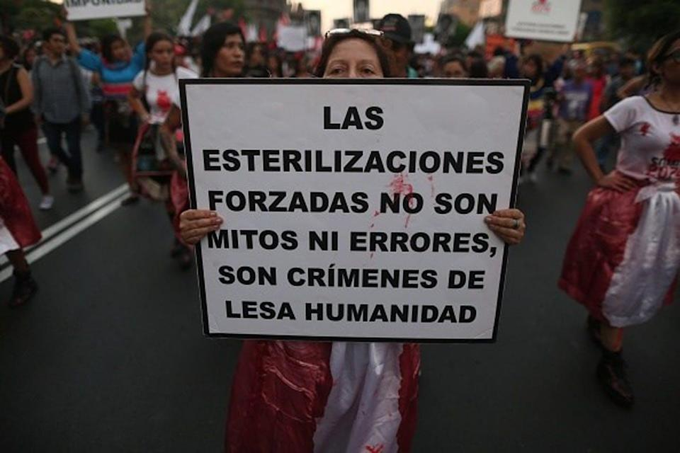 Peruvian protester holds a sign reading, 'Forced sterilizations are not myths or errors; they are crimes against humanity.'