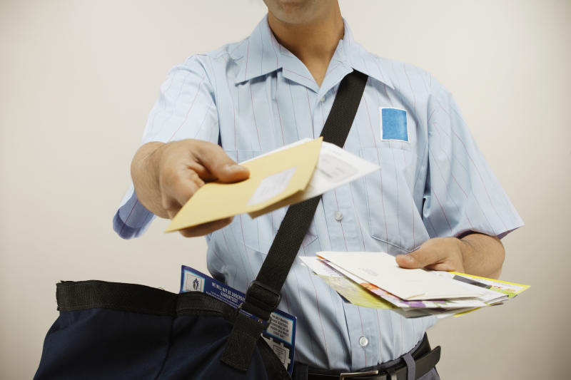 Photo shows postman delivering mail by hand
