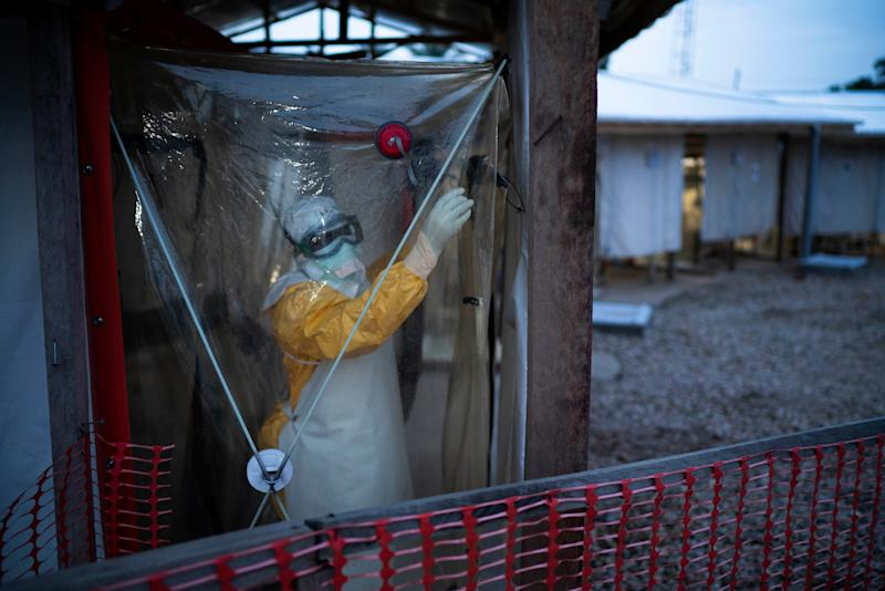 In this photograph taken Saturday July 13, 2019, an health worker wearing protective suits enters an isolation pod to treat a patient at a treatment center in Beni, Congo DRC. The head of the World Health Organization is convening a meeting of experts Wednesday July 17, 2019 to decide whether the Ebola outbreak should be declared an international emergency after spreading to eastern Congo's biggest city, Goma, this week. More than 1,600 people in eastern Congo have died as the virus has spread in areas too dangerous for health teams to access.