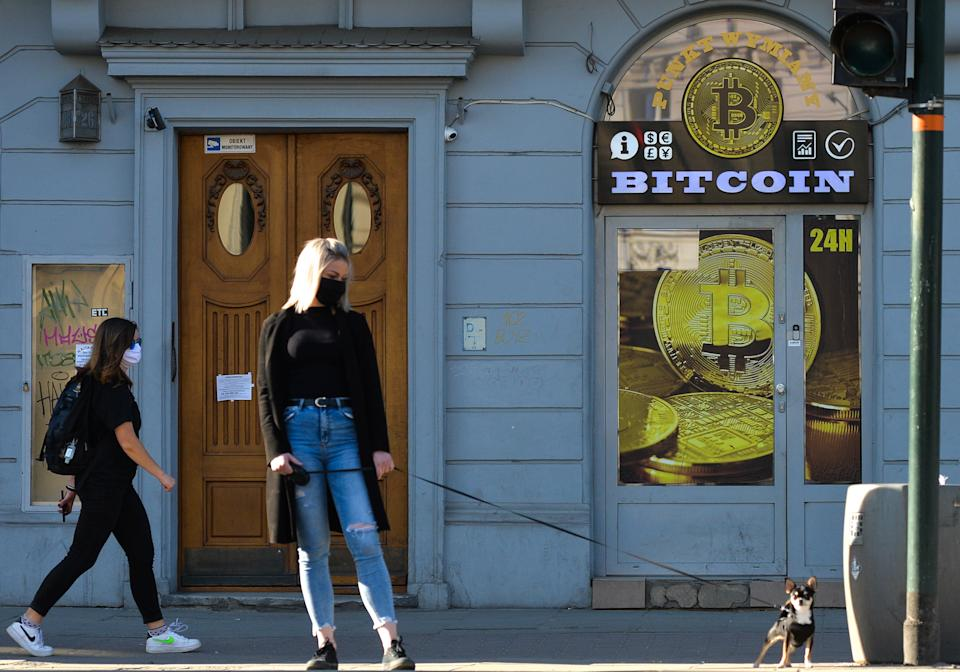 A lady wearing a protective mask walks her dog in front of a Bitcoin exchange shop in Krakow's city center.  On Saturday, April 18, 2020, in Krakow, Poland. (Photo by Artur Widak/NurPhoto via Getty Images)
