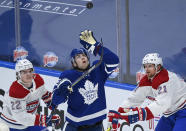Toronto Maple Leafs defenseman Ben Hutton (55) gloves the puck as Montreal Canadiens forwards Cole Caufield (22) and Eric Staal (21) watch during the third period of an NHL hockey game Saturday, May 8, 2021, in Toronto. (Nathan Denette/The Canadian Press via AP)
