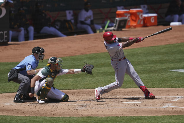 Los Angeles Angels' Justin Upton, right, hits a solo home run in front of Oakland Athletics catcher Austin Allen and umpire Mike Muchlinski (76) during the fourth inning of a baseball game in Oakland, Calif., Saturday, July 25, 2020. (AP Photo/Jeff Chiu)