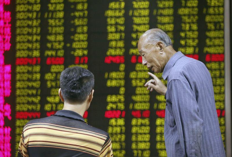 Investors talk in front of an electronic board showing stock information at a brokerage house in Beijing