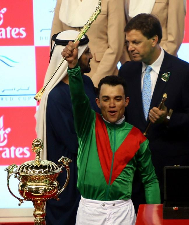 Jockey Joel Rosario raise the golden riding crop as he stands next to the trophy after leading Animal Kingdom to win the $10 million Dubai World Cup, the world's richest race, at Meydan race track in Dubai  March 30, 2013.  Animal Kingdom, the 2011 Kentucky Derby winner (11/2), trained by Australian Graham Motion and ridden by Rosario, beat home English raider Red Cadeaux by two lengths while another English-trained runner Planteur was third.            AFP PHOTO/MARWAN NAAMANI