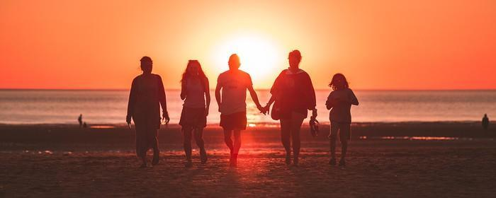 A family on a beach at sunset
