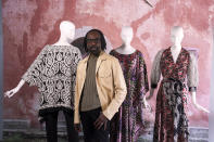 """Fashion designer Kevan Hall pauses for a picture at his """"Luxe Leisure Collection"""" haute couture atelier in West Los Angeles Thursday, March 18, 2021. Fashion retailers and designers had dramatically shifted their offerings more toward casual clothes and away from dressier items since the pandemic. A year ago, Los Angeles-based fashion designer Kevan Hall quickly moved away from his trademark gowns and cocktail dresses to caftans, tunics and pull-on pants. Now Hall is adding back some dressier looks, but he's eliminating the full skirts and scaling back the beading in favor of simple gowns and dresses in knit and tulle fabrics. (AP Photo/Damian Dovarganes)"""