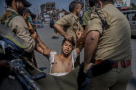 Indian policemen detain a Kashmiri Shiite Muslim for participating in a religious procession in central Srinagar, Indian controlled Kashmir, Tuesday, Aug. 17, 2021. Police in Indian-controlled Kashmir on Tuesday fired tear gas and warning shots to disperse hundreds of Shiite Muslims, while detaining dozens who attempted to participate in processions marking the Muslim month of Muharram. (AP Photo/Dar Yasin)
