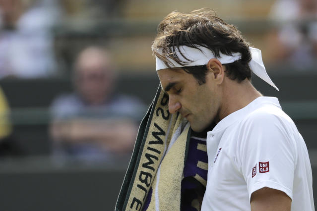 Switzerland's Roger Federer wipes his face after losing the fourth set of his men's quarterfinals match against Kevin Anderson of South Africa at the Wimbledon Tennis Championships, in London, Wednesday July 11, 2018. (AP Photo/Ben Curtis)