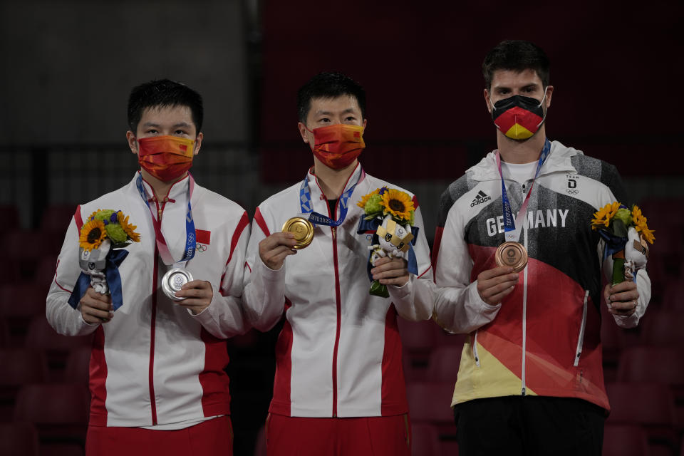 From left silver medalist Fan Zhendong of China, gold medalist Ma Long of China and bronze medalist Dimitrij Ovtcharov of Germany pose with their medals for the table tennis men's singles at the 2020 Summer Olympics, Friday, July 30, 2021, in Tokyo. (AP Photo/Kin Cheung)