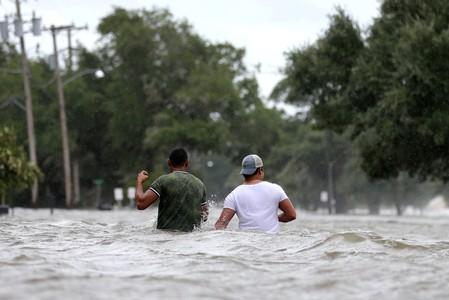 FILE PHOTO: People wade through a flooded street after Hurricane Barry in Mandeville