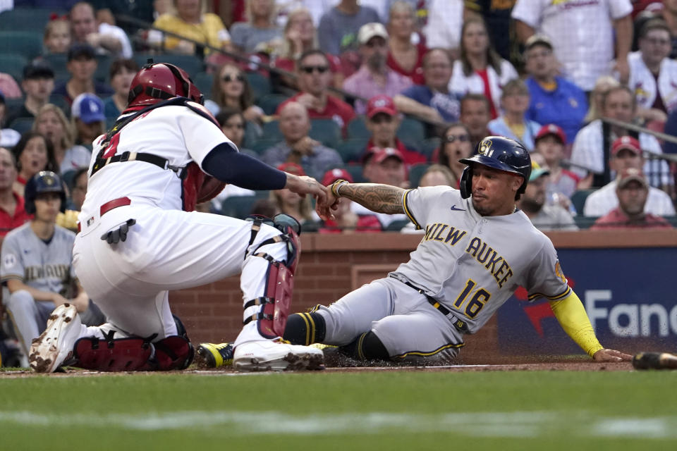 Milwaukee Brewers' Kolten Wong (16) is tagged out at home by St. Louis Cardinals catcher Yadier Molina during the first inning of a baseball game Tuesday, Aug. 17, 2021, in St. Louis. (AP Photo/Jeff Roberson)