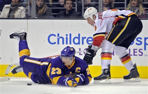 Los Angeles Kings right wing Dustin Brown, left, falls to the ice as Calgary Flames defenseman Jay Bouwmeester looks on during the second period of their NHL hockey game, Saturday, Feb. 18, 2012, in Los Angeles. (AP Photo/Mark J. Terrill)