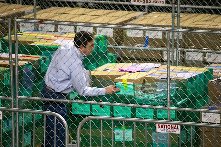 Ken Bennett, state Senate liaison for the Maricopa County election audit, helps package ballots from the 2020 general election to be moved from the Veterans Memorial Coliseum on May 14 in Phoenix, where they were examined and recounted by contractors hired by the Senate. The recount had to pause for various high school graduations scheduled at the coliseum.