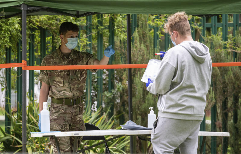 Members of the military operate a walk-in mobile Covid-19 testing centre at Spinney Hill Park in Leicester, England, Monday June 29, 2020. The British government is reimposing lockdown restrictions in the central England city of Leicester after a spike in coronavirus infections, including the closure of shops that don't sell essential goods and schools.  (Joe Giddens/PA via AP)