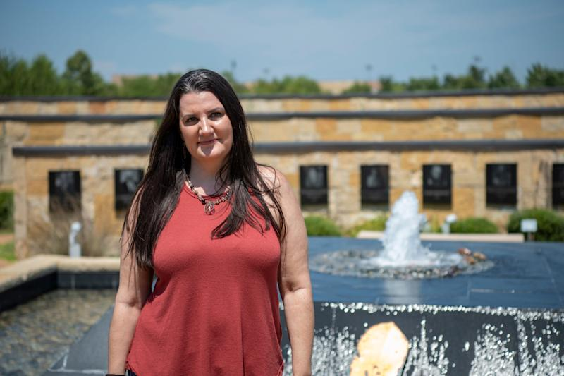 Shelby Rowe stands in the Aaholiitobli' Honor Garden at the Chickasaw Cultural Center in Sulphur, Oklahoma. Surrounding her are plaques honoring Chickasaw leaders, elders and warriors. Rowe has reconnected with her Chickasaw roots as part of her healing process.