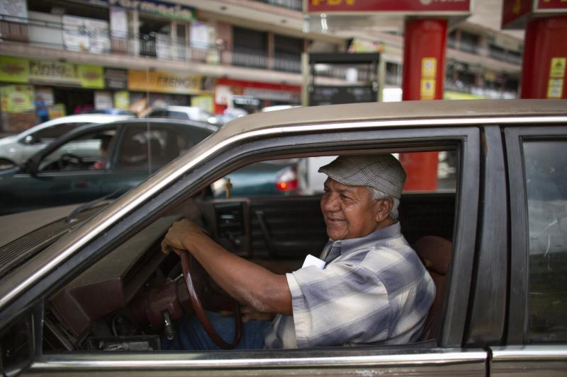 In this Oct. 8, 2019 photo, motorist Carlos Ortega waits as his car is filled up with gasoline by an attendant, who he paid in cash instead of bartering, at a gas station in San Antonio de los Altos on the outskirts of Caracas, Venezuela. Motorists in socialist Venezuela have long enjoyed the world's cheapest gasoline, with fuel so heavily subsidized that a full tank these days costs a tiny fraction of a U.S. penny. (AP Photo/Ariana Cubillos)