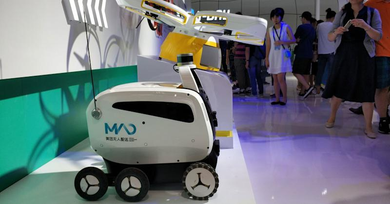 Visitors look at Meituan Autonomous Delivery drone and vehicle during the Smart China Expo at Chongqing International Expo Center on August 23, 2018 in Chongqing, China.