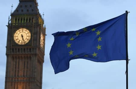 A European Union flag is waved in front of Big Ben and the Houses of Parliament in London