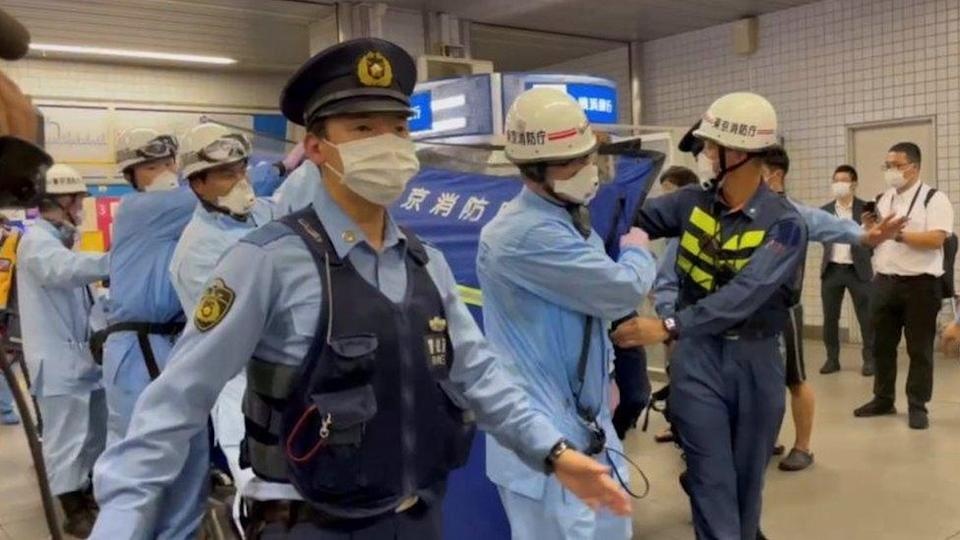 Police escort rescue workers carrying a person through a train station after a knife attack on a train in Tokyo