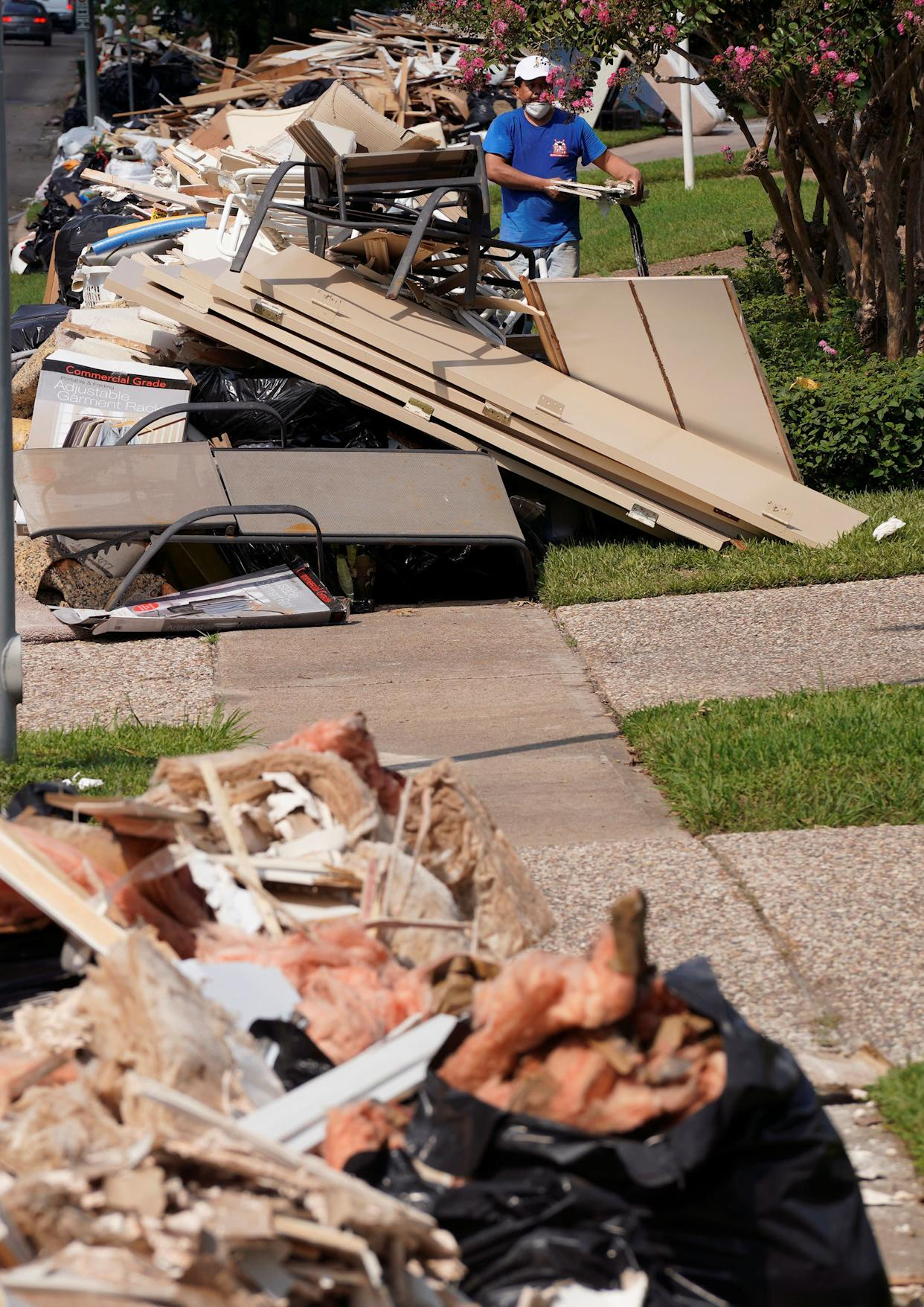 Giant mounds of trash from flood-damaged homes line a sidewalk on Sept. 2.