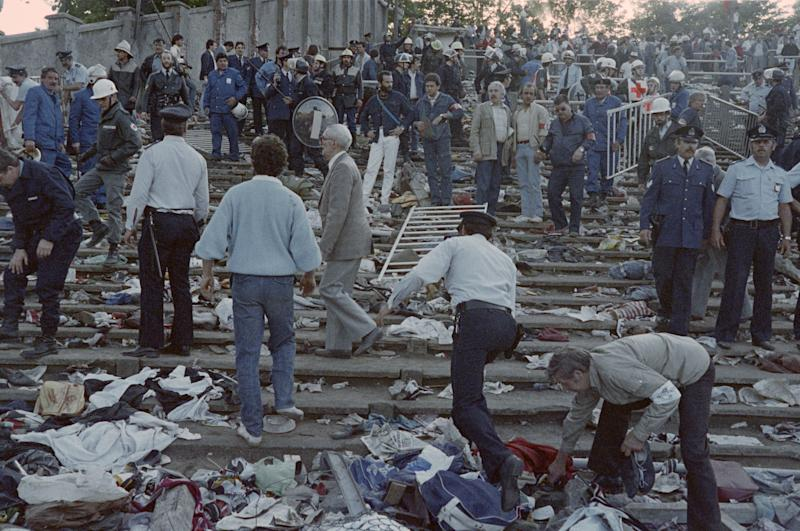 Rescuers and policemen search for victims on May 29, 1985 at the scene of riots in Heysel football stadium in Brussels after 39 people lost their lives in violent incidents, one hour before the European Champion Clubs final between Britain's Liverpool and Italy's Juventus of Turin. The tragedy occured when a wall collapsed in the stadium under the pressure of people and crushed Juventus fans as they tried to escape Liverpool supporters. (Photo by DOMINIQUE FAGET / AFP) (Photo by DOMINIQUE FAGET/AFP via Getty Images)