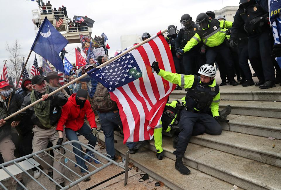 Members of U.S. Capitol Police try to fend off a mob of supporters of U.S. President Donald Trump as one of them tries to use a flag like a spear as the supporters storm the U.S. Capitol Building in Washington, U.S., January 6, 2021. Picture taken January 6, 2021. REUTERS/Leah Millis