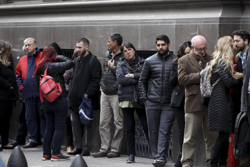 People wait for a bank to open in Buenos Aires, Argentina, Monday, Sept. 2, 2019. Argentina's government on Sunday decreed that Argentines will need authorization from the central bank to buy U.S. dollars in some cases and make transfers abroad for the rest of the year as it tries to prop up its peso currency. (AP Photo/Natacha Pisarenko)