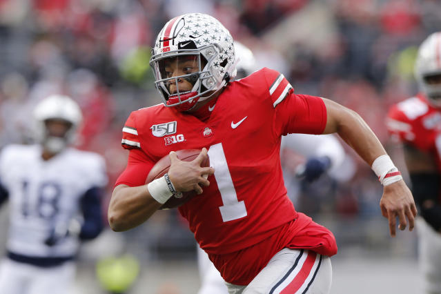 FILE - In this Nov. 23, 2019, file photo, Ohio State quarterback Justin Fields plays against Penn State during an NCAA college football game, in Columbus, Ohio. Fields, a sophomore and the Buckeyes Heisman Trophy finalist quarterback, said online classes allow him to split his time between studying at home or relaxing with Netflix and the Woody Hayes Athletic Center, where besides football facilities there is a new lavish lounge for players that offers made-to-order meals, massage chairs, video games on big screens and a cryogenic chamber. (AP Photo/Jay LaPrete, File)