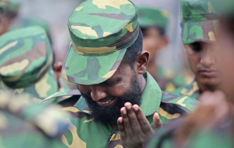 A Bangladesh army soldier cries he offers prayers for the souls of the 1,127 people who died in the garment building structure collapse last month, in Savar, near Bangladesh, Tuesday, May 14, 2013. The Islamic prayer service was held a day after the army ended the nearly three-week, painstaking search for bodies among the rubble of the worst tragedy in the history of the global garment industry and turned control of the site over to the civilian government for cleanup. (AP Photo/A.M. Ahad)