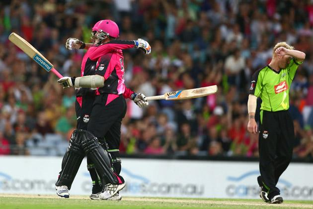 Daniel Hughes and Brett Lee of the Sixers celebrate victory as Scott Coyte of the Thunder looks dejected during the Big Bash League match between Sydney Thunder and the Sydney Sixers at ANZ Stadium on December 30, 2012 in Sydney, Australia.  (Photo by Mark Kolbe/Getty Images)