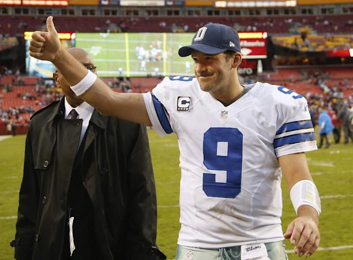Dallas Cowboys quarterback Tony Romo flashes a thumbs-up as he walks off the field after the Cowboys defeated the Washington Redsksins 24-23 in an NFL football game in Landover, Md., Sunday, Dec. 22, 2013. (AP Photo/Evan Vucci)
