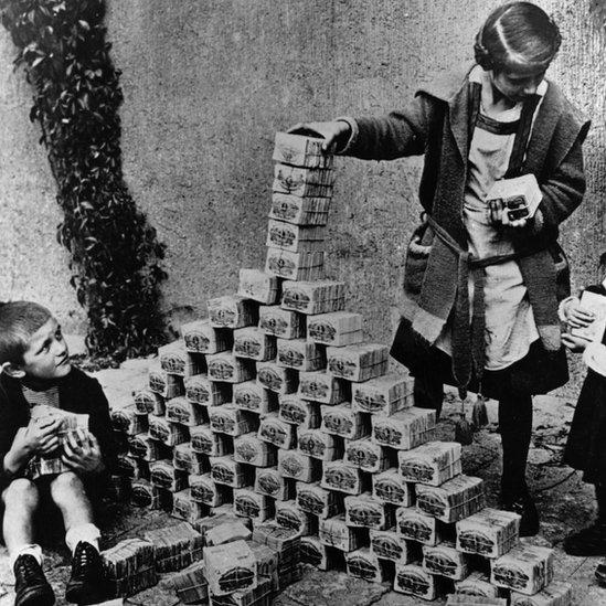 Children in Germany using reichsmark banknotes to build a tower in 1923
